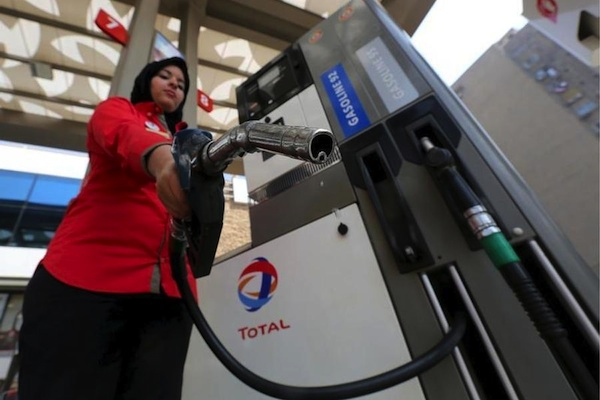 A female employee poses with a fuel pump at a petrol station in Cairo